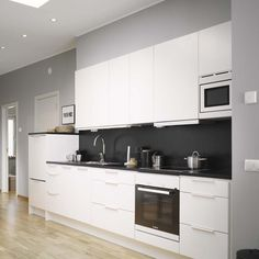 modern white kitchen with black wall maybe our fridge is just too big