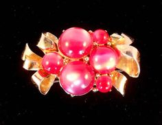 Eye catching brooch or pin by Coro featuring both large and small red moonglow lucite cherries in a cluster. Accenting that are ribbons of gold tone metal giving a feminine touch to this brooch. The brooch measures approximately 2 1/2 long by about 1 1/2 wide. Signed Coro on the back. Condition is good. There is some loss of the gold plating on the ribbon part. Shipped in a small box perfect for gift giving.  The item photographed is the exact one you will receive. Please consider ...