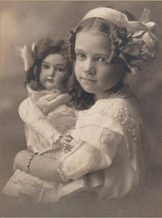 Girl with ribbon in her hair, and bracelet, cuddling her doll.