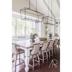 Two lanterns over kitchen island in White Kitchen with Vaulted Ceilings | Design Julie Couch Interiors, Photo Alyssa Rosenheck