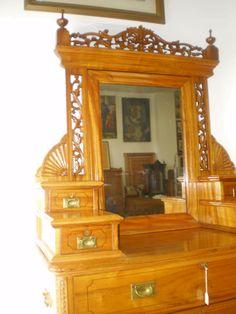 Cómoda - tocador con espejo de barco en alcanfor tallado. Inglaterra, Siglo XIX. 4 cajoncitos superiores y 4 cajones inferiores irregulares en su tamaño. Se divide 3 en piezas. Llaves y cerraduras originales funcionando. 225 x 52 x 122 cm.