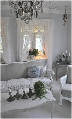 Shabby Chic Livingroom. Linen(?) sofa and chair!!! Candle holders!!! And the shelf that was added to the windows. Doesn't look like a window sill but maybe an addition.
