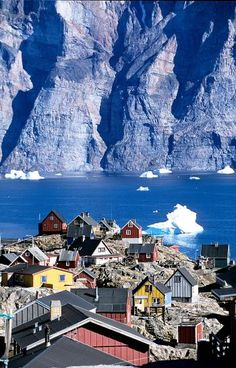 Colorful homes overlook a large cliff across the water along the shore of Greenland. Photo by Jens Henrick Nybo