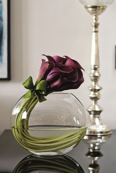 Dark burgundy callas curved in a sphere vase with a ribbon that matches the stem color.  Very cool centerpiece.