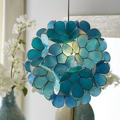 Symbolizing purity while providing pure brilliance, this Daisy Capiz Pendant Light is a shimmering natural. The source of its beautiful blue glow? Capiz shells painted aqua and teal then hand-forme… Decor, Powder Room Sink, Capiz, Coastal Lighting, Lamp, Ceiling Lights, Pendant Lamp, Pendant Light, Light