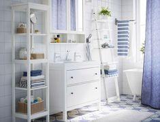 Bagno bianco con mobile per lavabo, scaffale e mobile a specchio HEMNES bianchi, tenda doccia blu e asciugamani bianchi e blu.