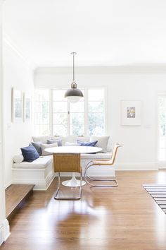 A Bright and Modern Sunroom Intro // white and bright sunroom with built in banquet, round white table, and two wicker chairs.