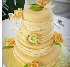 The four-tier vanilla cake with strawberry preserve filling was made by Brenna's cousins in their Chicago bakery and driven all the way to Louisville for the wedding. The delicious dessert was adorned with sugar peonies, fondant ribbon, and Brenna an...