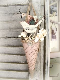 This Victorian style Paper cone, or tussie mussie is in a soft pale blush color, and is the perfect complement to the upcoming Spring season, with its adorable shabby white bird made from vintage sheet music, layered paper rosette flower, vintage buttons, tiny flowers, layers of tattered ribbon and the miniature banner which reads SING. It would be perfect all the way through summer adorning a cabinet, door knob or special wall hook. It measures (including the banner, all the way to the tip…