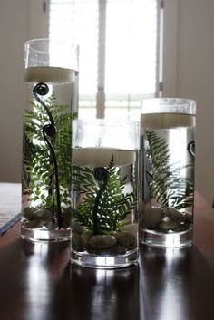 Unique centerpiece using trio of cylinder vases - river rocks, submerged fern leaf and fiddlehead and floating candle on top