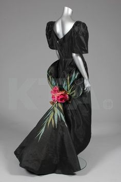A Ramon Valera black gazar evening gown, or `Terno', Philippines, late 1950s, with `butterfly' sleeves, pleated overskirt forming a puff-ball swag-effect to the back, culminating in large silk roses with appliqued foliage in shades of green.