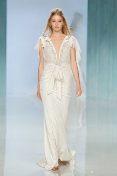 """Flowy wedding gown with a bowtie in the front and plunging neckline // In our second feature on our favourite designers at Barcelona Bridal Fashion Week 2017 which we covered as an Official Media partner, we fix our gazes on Galia Lahav's bohemian Gala No. IV line and dramatic Victorian Affinity 2018 collection. The standout pieces for us on the catwalk? """"Thelma"""", a homage to Queen Victoria's wedding gown with sheer drape silk tulle sleeves and """"Liliya"""", a fairytale ball gown made of real…"""