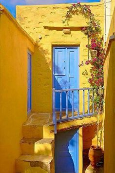 Yellow houses and blue doorsteps just go together! Greece is looking so cute with all their colorful doorsteps!