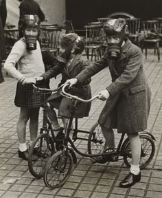 Children on bicycles, wearing gas masks, 1940s