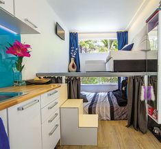 Interior view of a shipping container granny flat, with living area above bed, small