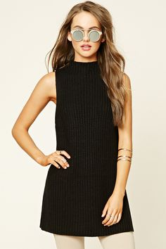 A sleeveless ribbed knit sweater featuring a high neckline and high side slits.