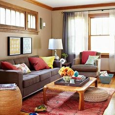 Heather- the pops of orange and blue work well with the brown sofa.  I like the idea of an accent pillow or throw on the chair, too.  Mix and match pillows and throws on the sofa and chair.  The one yellow pillow is nice too!  Notice the wall color with the wood trim too!  Click photo to see other rooms with a brown sofa.