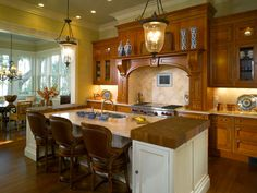 Interesting incorporation of cutting boards onto island. Clive Christian Luxury Kitchen in Antique Yew Wood and Classic Ivory