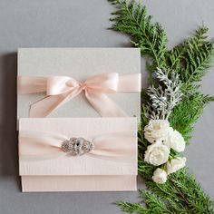 Blush colored silk wrapped folio with two layers of ribbon and a beautiful large rhinestone brooch.  Gorgeous luxury wedding invitation mailed in a glitter box.