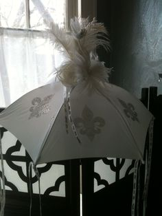 """Fleur de lis, plumes, and """"Happily Ever After"""" ribbon adorn this bride's second line umbrella created by All About Events www.allaboutevents.net"""