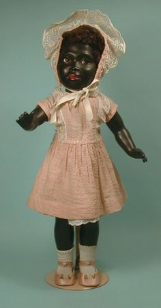 "Rare German black plastic doll, 17"", circa 1950. She has glass flirty eyes that go from side to side and also sleep. Human hair lashes make this doll highly collectible."