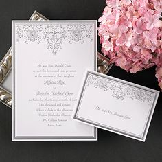 A bright white invitation card features a rich silver border with silver heart and filigree design at the top with gold accents.