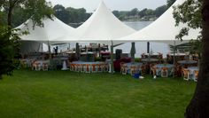 Beautiful century tent setup on the lake for a wedding. The white padded folding chairs have bright orange satin sashes tied onto them.