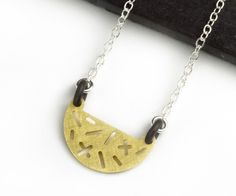 Half-moon, half-round, modern and geometric necklace from Camillette Jewelry. Random pattern of cut out lines. Camillette.com