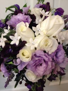 Brides bouquet with white roses, white stephanotis with crystal centers, purple lisianthus, and lavender
