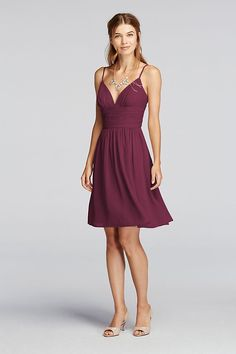 This delightful short chiffon bridesmaid dress has a uniquely curved deep V-neckline and delicate spaghetti straps.   A ruched bodice combined with a flowing skirt  will compliment your figure.