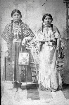Nez Perce teen girls wearing beautiful traditional dresses and holding beaded bags -  circa late 1800's - early 1900
