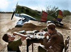 Incredible colourised photos have been unearthed showing international volunteers in the Spanish Civil War. Pictured, troops at resting for a meal in front of a Polikarpov I-16 'Rata' aircraft at the Els Monjos Aerodrome in the Province of Barcelona in 1938