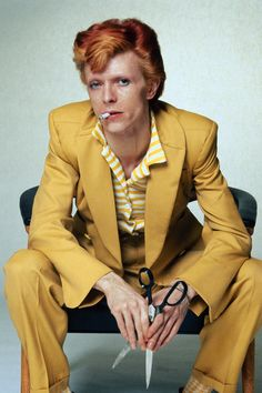 Bowie poses with his newly dyed red hair in a bright yellow suit.    - HarpersBAZAAR.com