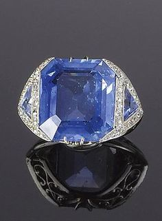 An art deco sapphire and diamond ring, circa 1925 The large octagonal-shaped sapphire, between shoulders set with trillion-cut sapphires, each surrounded by single-cut diamonds within millegrain settings, to a pierced gallery, principal sapphire approximately 17.00 carats