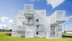 White caged balconies project from the sides of this social housing block by French collective Poggi + More, making it look like a series of irregularly stacked boxes.