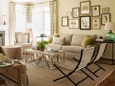 Lauren Liess - Stunning living room with framed sea life gallery wall over sofa on walls painted in Seashell by Benjamin Moore. A pair of woven rope chairs stand in front of the trestle coffee table over a bound sisal rug layered on hardwood floors.