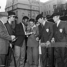 Brazilian footballer Pele signing autographs for members of the French squad at Lancaster House, London, after attending the reception for teams already eliminated from the World Cup, 21st July 1966.○
