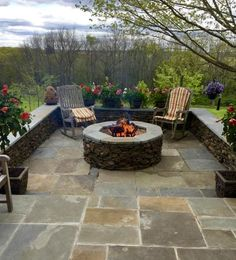 Large round masonry firepit with natural stone veneer.