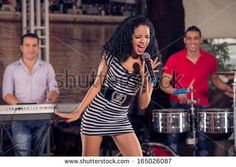 Image of an adorable singer performing emotionally on the stage with the music band on the foreground - Shutterstock Premier