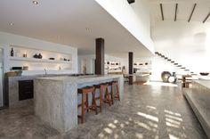 Open space molto particolare, stile moderno minimal - cucina in muratura con strutture in cemento, così come il pavimento - tutto abbinato al legno massello del tavolo sala pranzo, scala sospesa, sedie e vari travi
