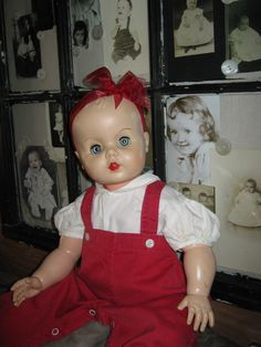 Old doll from the 50's wearing vintage baby clothes