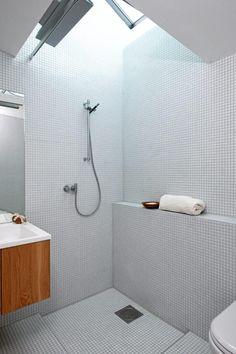 Overlyset fra vinduet siver ned i dusjen, som er kledd med mosaikkfliser fra Bisazza. Innredning i eik er fra Holedesign. Fin og praktisk hylle ved dusjen. Selve dusjsonen er nedfelt som et kar. Styling: Tone Kroken.