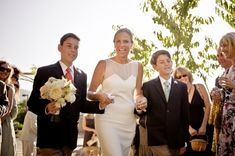 mature bride walks down aisle with sons