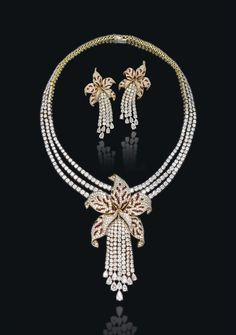 THE RUBY AND DIAMOND 'ORCHID' PARURE, BY CARTIER Comprising a brilliant-cut diamond three row necklace suspending at the front a detachable sculptural calibré-cut ruby and pavé-set diamond orchid flower with a brilliant-cut diamond tassel pistil (can be worn as a brooch), a pair of ear pendants en suite, 1989  2