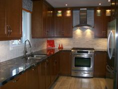 Compact contemporary beautiful kitchen. medium wood tones with tumbled marble back splash and cosmic granite counter tops.