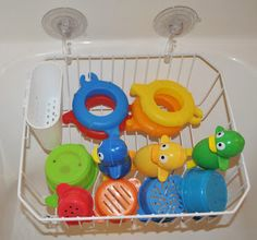 What a cool idea. Using a dish drying rack as a bath toy storage system. just use suction cups to attach it to the shower wall. Easy drainage, no mold/mildew. spray with disinfecting spray and walk away. also has a little cubby for silverware which could be used for bath crayons and other tiny things. GREAT idea!