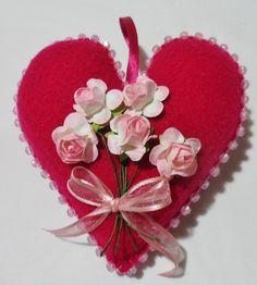 corazón fucsia oscuro, con bordado de mostacillones, ramo de flores de papel en tono rosa y cinta de gasa.