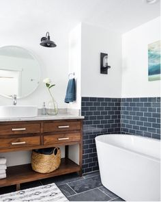 Navy subway tile adds contrast against while walls to this bathroom with a standalone tub and wood vanity. Subway tile doesn't have to be white - add a unique, bright, or even subtle color to a bathroom or kitchen by adding colored subway tile!