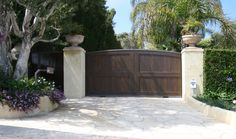 driveway gate | Driveway gates in dark wood are popular for homeowners whose house ...