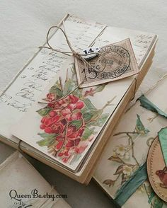 A stack of vintage books, altered, white washed, distressed and adorned with a page from an old ledger, antique floral postcard, and brass number tag all bundled together with a natural twine. The richest of reds, neutrals and the shabbiest of whites for a truly vintage, romantic look. Set our on a coffee table, alongside other antique books, or on a nightstand. True vintage at its best! The book stack measures 8 x 5 1/2 x 2 inches. *Any overcharge in shipping will be promptly refunded o...